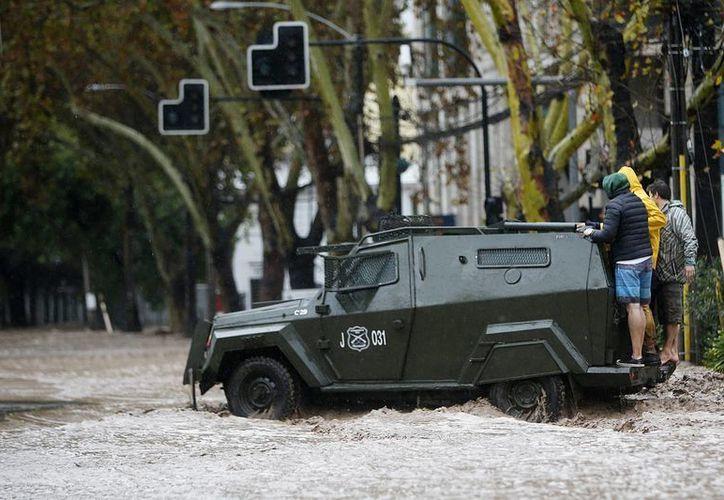 """Policías rescatan personas debido a las lluvias en la región metropolitana, donde la autoridad ha decretado """"alerta roja"""", cuando más de cuatro millones de personas se encuentran sin suministro de agua potable, y cientos de calles se encuentran intransitables. (EFE)"""