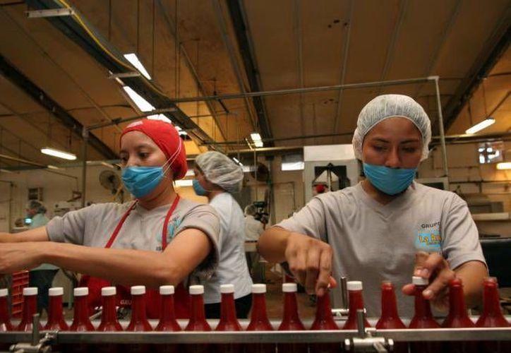 Empresarios yucatecos apuestan por la reindustrialización en la entidad. Imagen de un par de trabajadores en una fábrica. (Milenio Novedades)