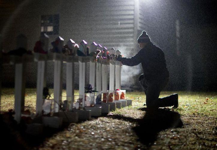 Frank Kulick, ajusta una exhibición de cruces de madera, y una estrella judía de David, que representa a las víctimas del tiroteo en la escuela. (Agencias)