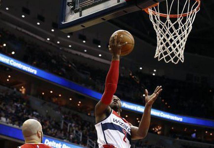 John Wall (2), guardia de Wizards, lanza un disparo en partido en el que su equipo ganó a Atlanta para llegar a 46 victorias, un récord de la franquicia en la NBA. (Foto: AP)