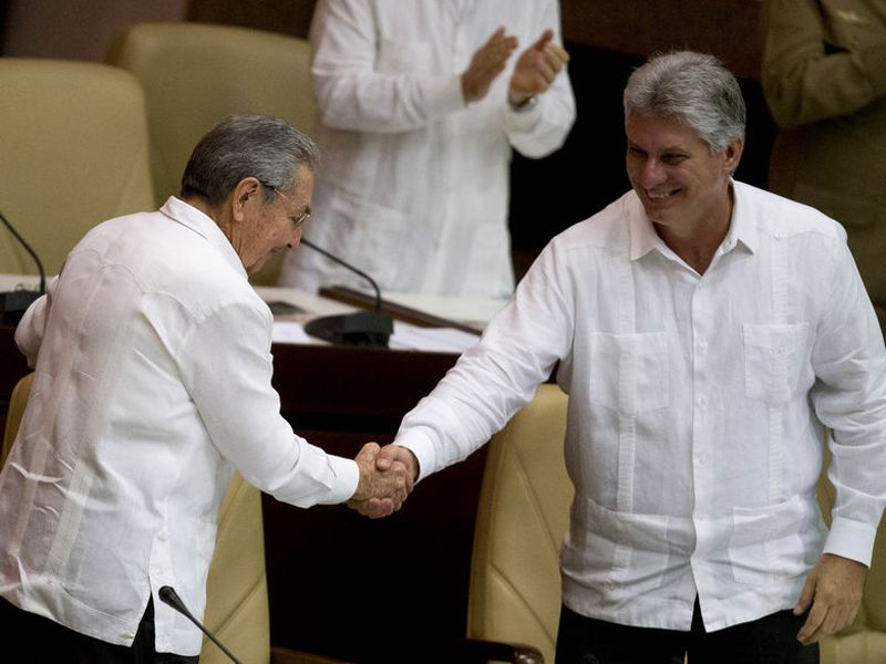 Cuba's President Raul Castro, left, shakes hands with Vice President Miguel Diaz-Canel, at the closing of the legislative session at the National Assembly in Havana, Cuba. (AP).
