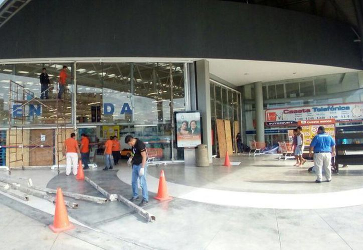 Los trabajadores colocan tablas para evitar actos de vandalismo. (Eric Galindo/SIPSE)