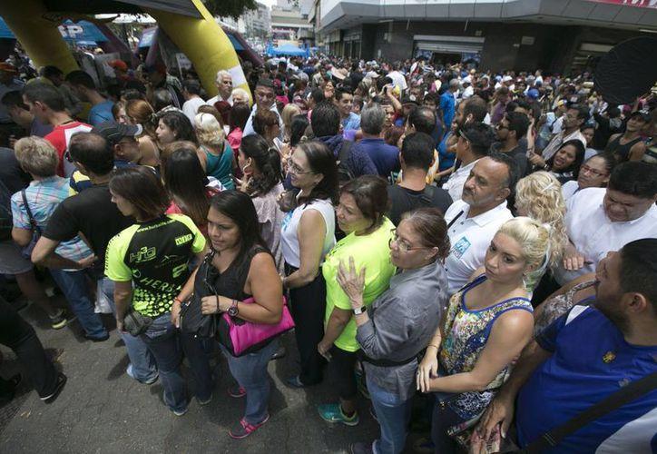 Cientos de personas hacen fila para firmar por el referéndum revocatorio al presidente Nicolás Maduro, que organiza la oposición, ayer en Caracas, Venezuela. (AP/Ariana Cubillos)