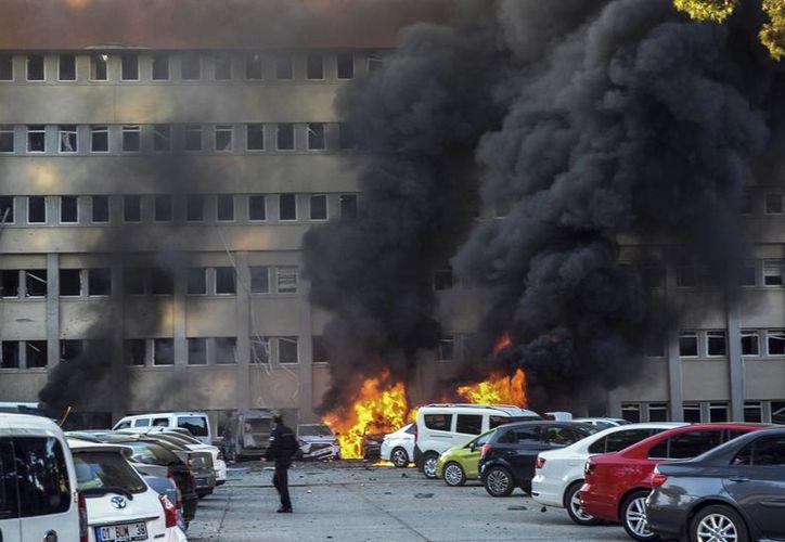 Un agente de policía pasa junto a un incendio tras una explosión en la ciudad de Adana, en el sur de Turquía. (AP)