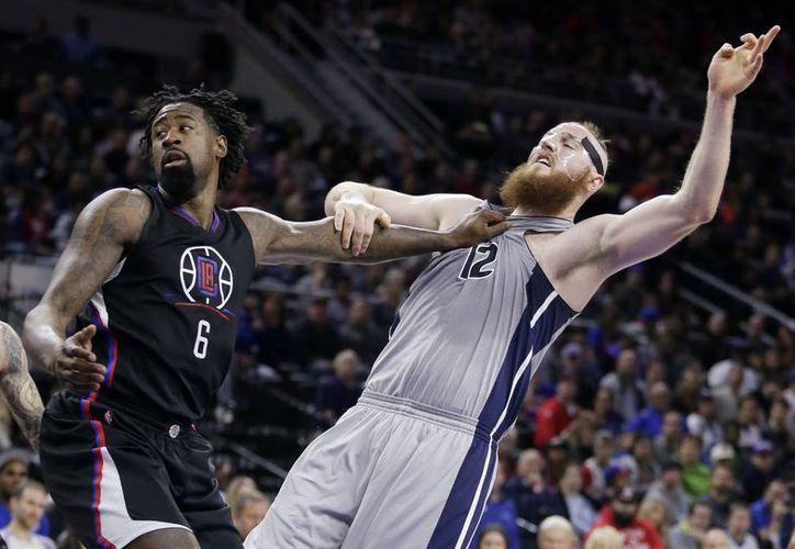 Aron Baynes (12), de Pistons, es jaloneado por DeAndre Jordan (6), de Clippers, en partido ganado por este último equipo. (AP)