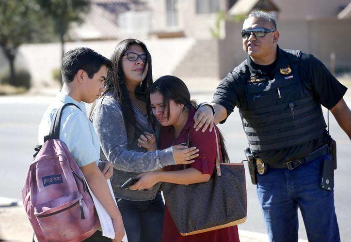 Los estudiantes se abrazan después de salir de la escuela, el viernes, 12 de febrero, 2016, en Glendale, Arizona. Después que dos adolescentes fueron abatidos el viernes en Independence High School en el suburbio de Phoenix. (Foto AP / Matt York)