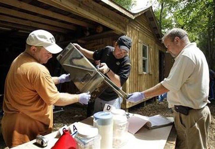 Policías estudian las pruebas en un presunto laboratorio de metanfetamina en Gerald, Misuri. (Agencias)