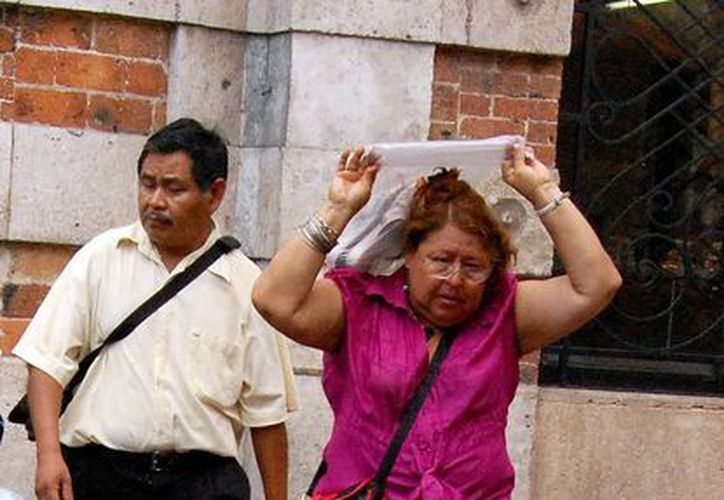 Transeúntes se protegen de la lluvia que cayó ayer en Mérida. (Wilberth Argüelles/SIPSE)