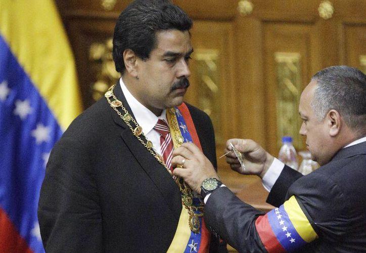 Diosdado Cabello impone la banda presidencial a Nicolás Maduro. (Agencias)
