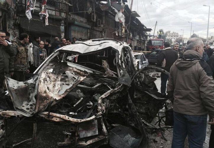 Ciudadanos sirios se reúnen junto a coches dañados en la escena donde la explosión golpeó una calle comercial, en la ciudad costal de Jableh, Siria. (SANA vía AP)