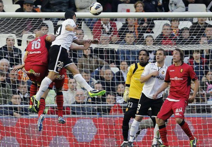 El defensa del Valencia CF Ricardo Costa bate al portero del Real Mallorca, Dudu Aouate.  (EFE)