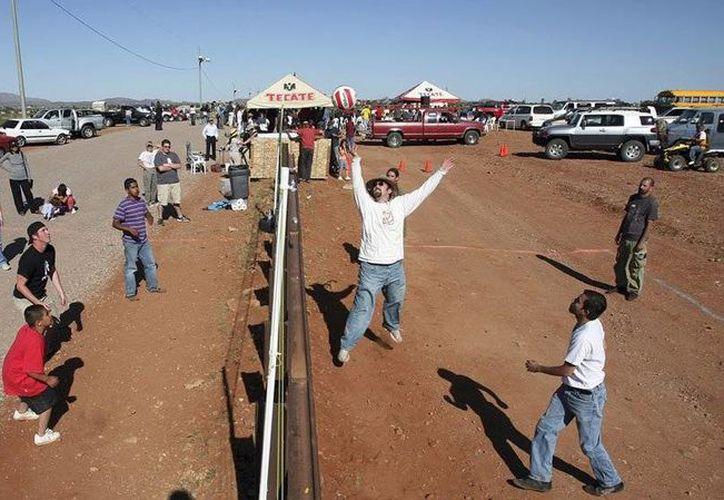Los residentes de Naco, Arizona, se unen a los residentes de Naco, México, para un partido de voleibol en la valla que separa a Estados Unidlos (izq) y México. (taringa.net)