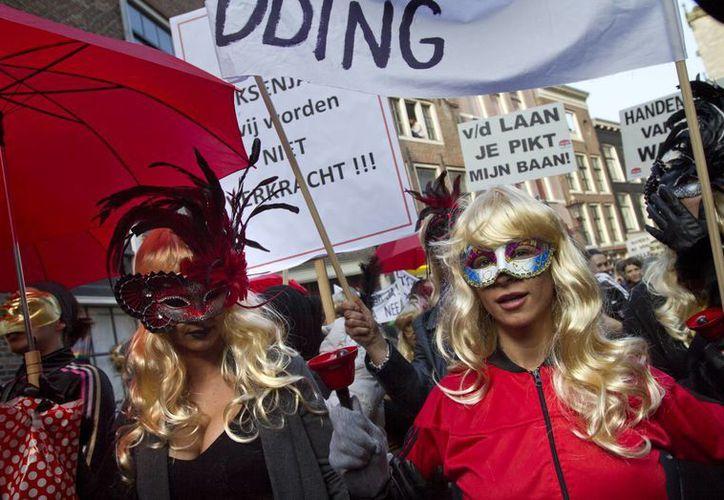 Sexoservidoras y sus partidarios, todos con máscaras, marcharon a través de la Zona Roja de Amsterdam para pedir que no clausuren los escaparates en que se exhiben. (Foto: AP)