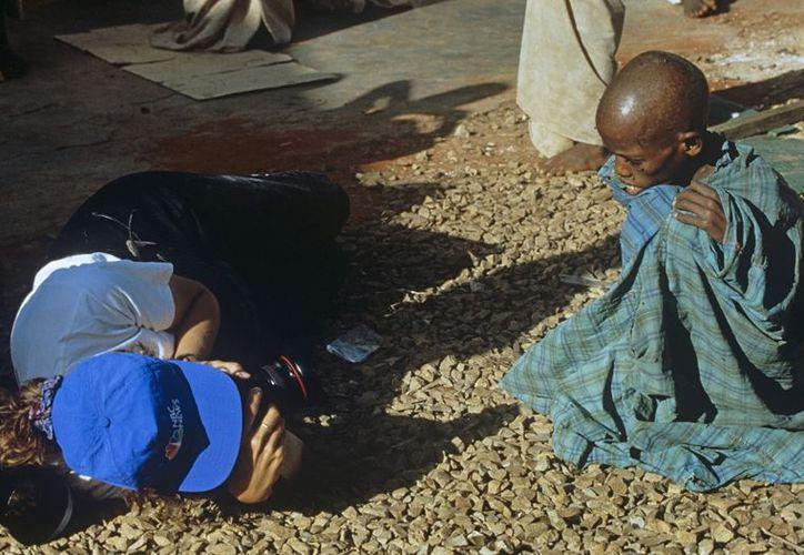 Un reportero gráfico se tumba en el suelo para fotografiar a un niño somalí en la ciudad de Badoia. (EFE)