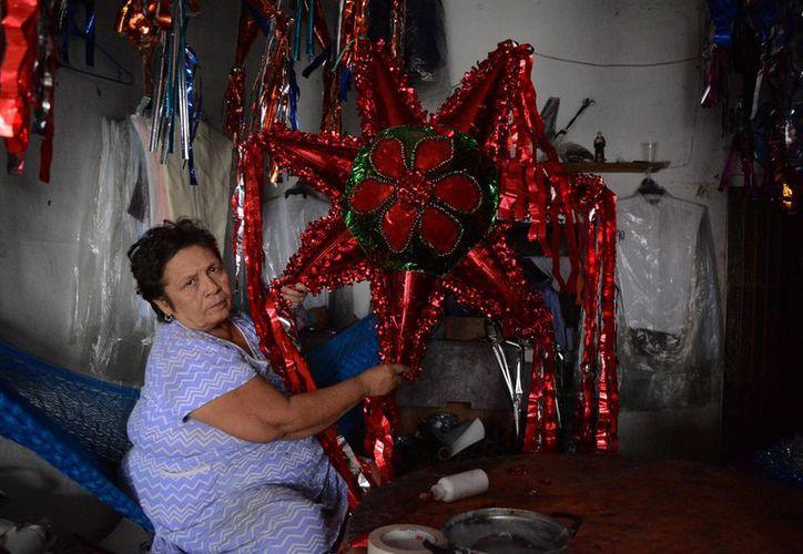 """Doña Rosario Medina muestra un modelo de la piñata más demandada en esta época: la estrella con sus """"picos"""".  (Fotos de Victoria González/SIPSE)"""
