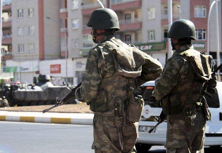 Soldados turcos vigilan en una de las principales carreteras tras declararse un toque de queda tras los disturbios registrados durante una manifestación en Diyarbakir, en el sureste de Turquía. (EFE/Archivo)