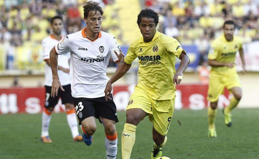 Dos Santos controla la pelota ante el centrocampista del Valencia, Sergio Canales durante el partido. (EFE)