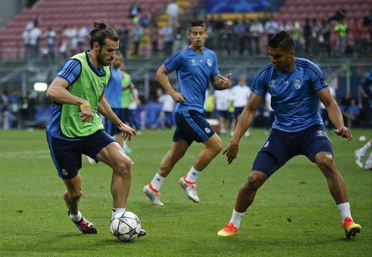 El galés Gareh Bale (i), que próximamente jugará la Eurocopa por primera vez en su vida con Gales, durante un entrenamiento del Real Madrid previo a la final de la Liga de Campeones de Europa. (Fotos: AP)