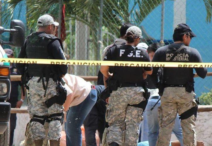 Imagen del momento en que autoridades realizan los peritajes del doble homicidio en Dzi. (Milenio Novedades)