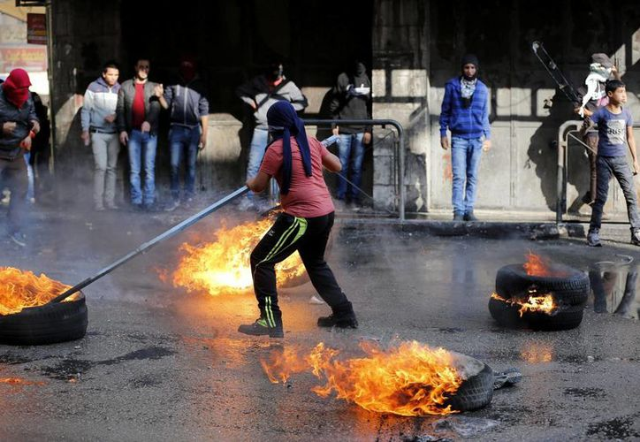 En la imagen, manifestantes palestinos queman neumáticos durante enfrentamientos con las fuerzas de seguridad israelíes en la ciudad cisjordana de Hebrón. (EFE)