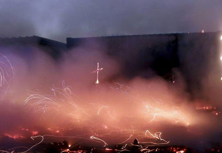 Imagen de las llamas ardiendo en el campamento migrante improvisado conocido como 'La Jungla' cerca de Calais, en el norte de Francia, este el martes 25 de octubre de 2016. (AP Foto/Thibault Camus)
