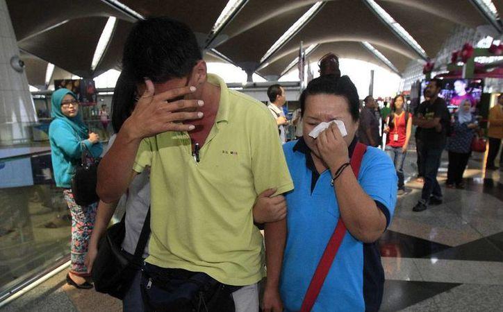 Pasajeros del avión de Malasya Airlines que desapareció ayer de los radares llevaban pasaportes falsos, lo que ha levantado sospechas de terrorismo. En la imagen, familiares de los viajeros, desconsolados por la noticia de la desaparición de la aeronave. (Agencias)