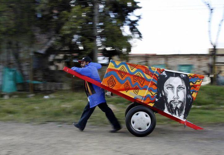 Un reciclador de basura tira de una carreta pintada por la artista colombiana Lorena Correa como parte de un proyecto artístico y social en Bogotá. (Agencias)