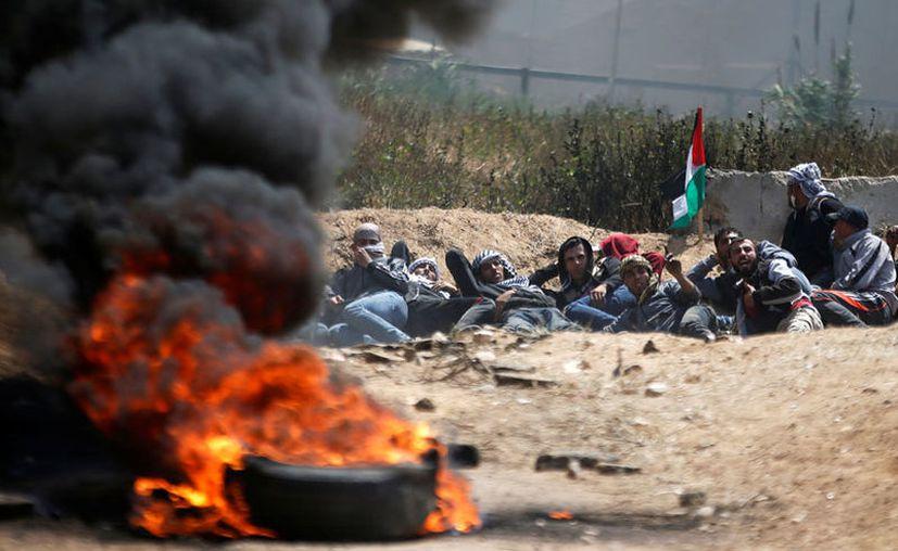 Los jóvenes siguen con la quema de llantas que estuvieron recogiendo durante la semana. (Reuters)