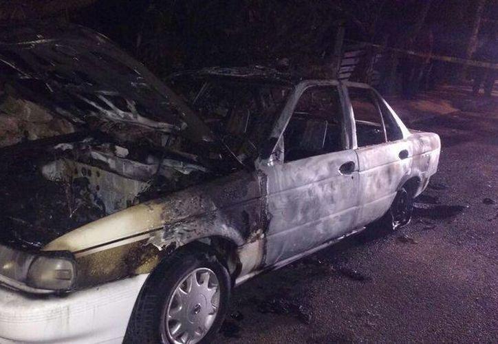 El taxi fue incendiado en la colonia San Marcos Nocoh. Los agresores huyeron con el efectivo y dos celulares del chofer. (SIPSE)