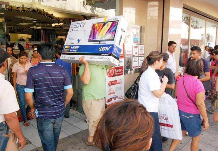 Miles de personas salen a las calles a realizar compras navideñas con los aguinaldos que reciben en estos días. Imagen de un grupo de personas que salen de una conocida tienda departamental en Mérida. (Milenio Novedades)