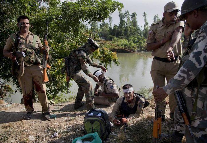 Un soldado del ejército indio, segundo de la izquierda, asiste a soldados paramilitares lesionados en una emboscada en una carretera en Pampore, en las afueras de Srinagar. (Agencias)
