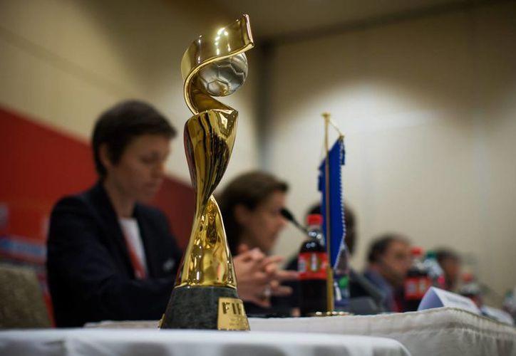 A primera vista se observa el trofeo que obtendrá la selección campeona del Mundial femenil de futbol, que hoy dio inicio en Vancouver, Canadá, en el marco de una crisis que afecta a la FIFA por corrupción y sobornos. (Foto:AP)