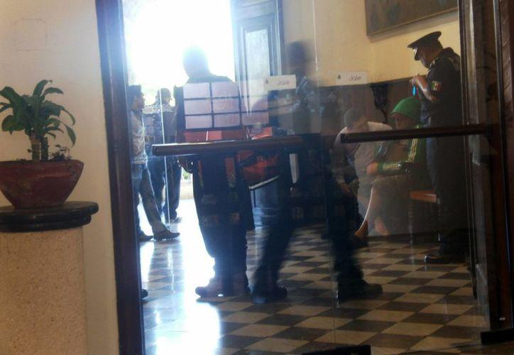 Policías y regidores del Ayuntamiento de Mérida interrogan al hombre que arrojaba el dinero desde el Palacio Municipal. (Daniel Martínez/SIPSE)