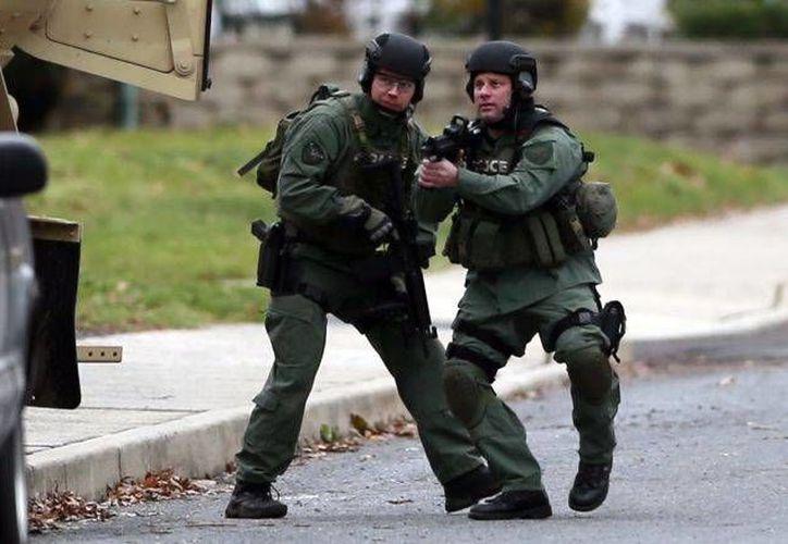 Dos agentes de la policía de Philadelphia llegan a la zona donde estaría atrincherado el sospechoso de tres tiroteos que dejaron un saldo de cinco muertos la madrugada del lunes en las afueras de la ciudad. (Agencias)