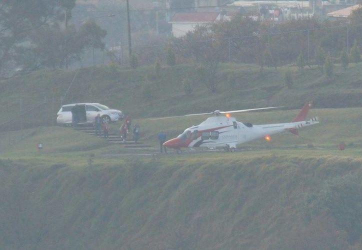 Un grupo de personas -entre ellas varios niños– desciende de una camioneta de lujo color gris, mientras la aeronave de la dependencia gubernamental espera a sus pasajeros en un área verde. (facebook.com/creswinman)
