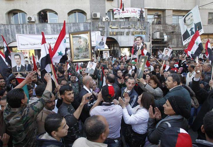 Manifestantes pro-gobierno sirio sostienen fotos del presidente sirio, Bachar Al Assad, durante una manifestación en Damasco, Siria. (EFE)