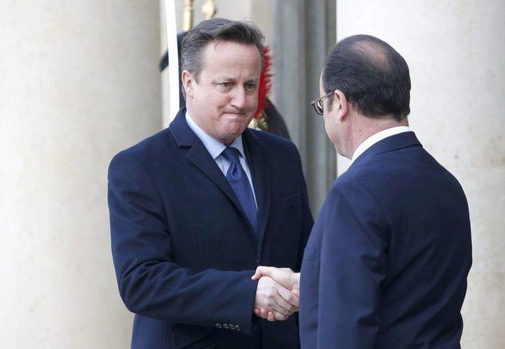 El presidente francés, Francois Hollande (d), da la bienvenida al primer ministro británico, David Cameron (i), en el Palacio del Eliseo en París. (EFE)