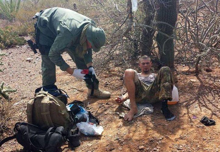 Los migrantes dijeron a los agentes fronterizos que habían estado deambulando en el desierto durante varios días. Imagen de archivo de un agente de la Patrulla Fronteriza al momento de rescatar a un ilegal. (AP/Archivo)