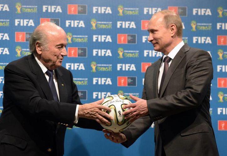 Joseph Blatter recalcó que se tiene que trabajar más en la discriminación en los estadios. En la imagen, el líder de FIFA sostiene un balón brazuca con el presidente de Rusia, Vladimir Putin. (AP)