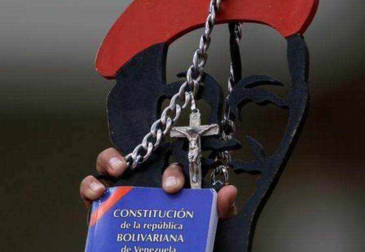 Un partidario de Hugo Chávez muestra un diseño del rostro del mandatario, un crucifijo y un ejemplar en miniatura de la Constitución, durante una demostración de en su apoyo, el 5 pasado de enero en Caracas. (AP)