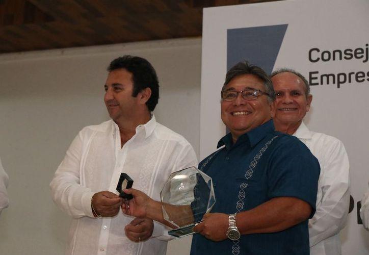 José Acosta recibió su premio de manos del presidente de la Canaive. (Daniel Sandoval/Novedades Yucatán)