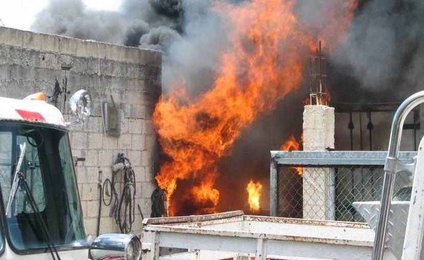 El fuego consumió tres vehículos que estaban dentro del taller mecánico. (Redacción/SIPSE)