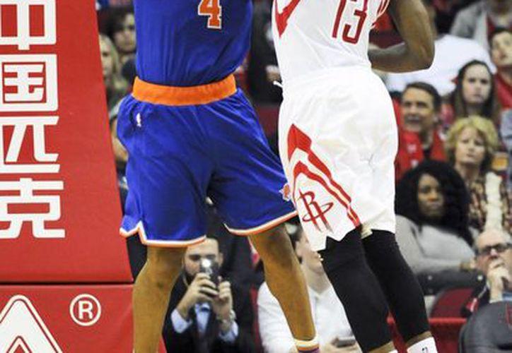 El guardia de Knicks, Arron Afflalo (4), lanza el disparo mientras James Harden (13), guardia de Houston Rockets, trata de evitarlo. Al final ganó el conmunto de Nueva York. (AP)