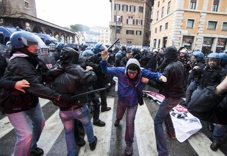 Fuera del Senado italiano se registraron enfrentamientos entre la policía y manifestantes que se oponen a la reforma laboral. (EFE)