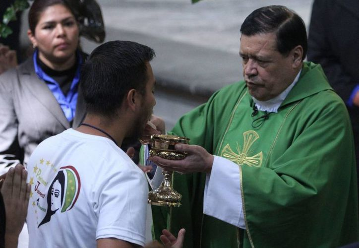 Norberto Rivera también oró por los ciudadanos, policías y elementos de las Fuerzas Armadas que han perdido la vida en el combate contra la delincuencia organizada. Imagen de contexto del cardenal al momento de la comunión. (Archivo/Agencias)