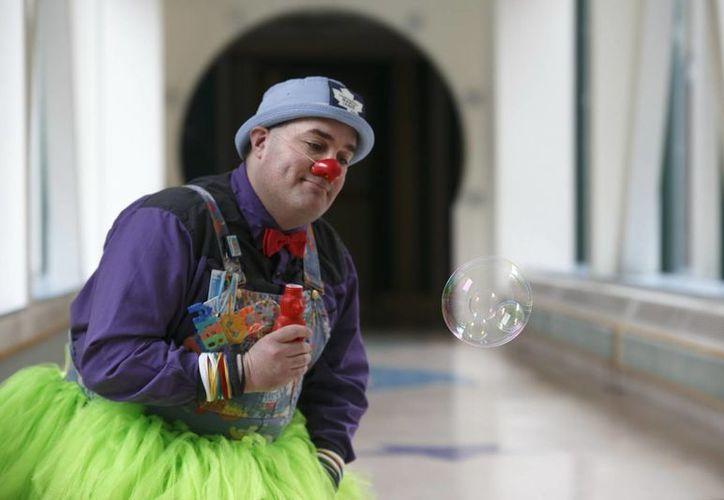 El payaso terapéutico A. Leboo, residente del hospital pediátrico SickKids, juega con pompas de jabón en uno de los pasillos del hospital en Toronto, Canadá. (EFE)