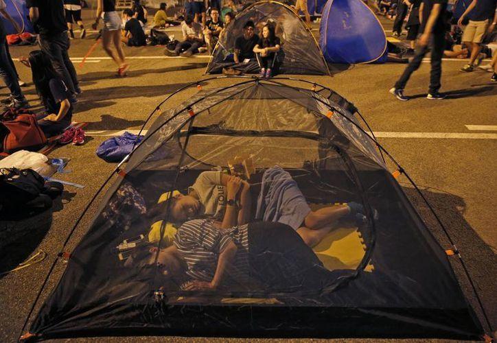 Manifestantes prodemocráticos duermen en una calle principal después de un mitin en las zonas ocupadas fuera de la sede del gobierno en Almirantazgo de Hong Kong. (Agencias)