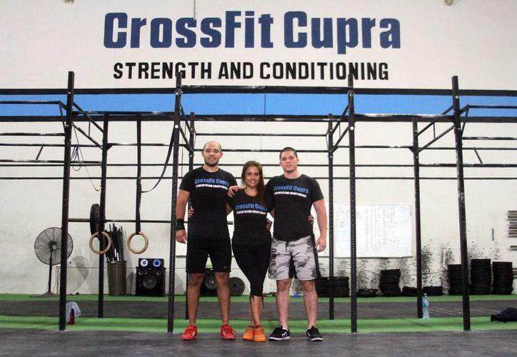 Imagen de Nonny de Leija, Aarón Cerón Llañez y Carlos Estébanez Escalante, los fundadores de CrossFit Cupra. (César González/SIPSE)