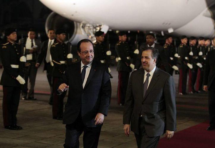 El presidente francés Francois Hollande con el secretario de Relaciones Exteriores, José Antonio Meade, tras descender de su  avión en el Aeropuerto Internacional de la Ciudad de México. (Agencias)