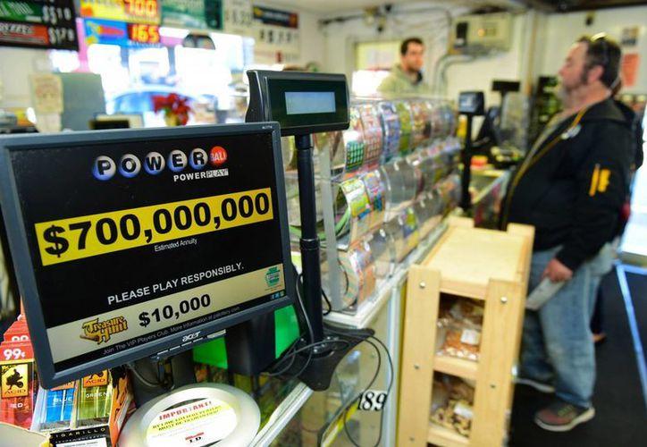 Un hombre compra billetes de la lotería Powerball, la cual tiene un acumulado de casi 700 mdd. (Agencias)